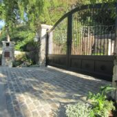 Gated entrance to a beautiful property with the pillars of the gate and the driveway being built with bluestone cobblestone brick.
