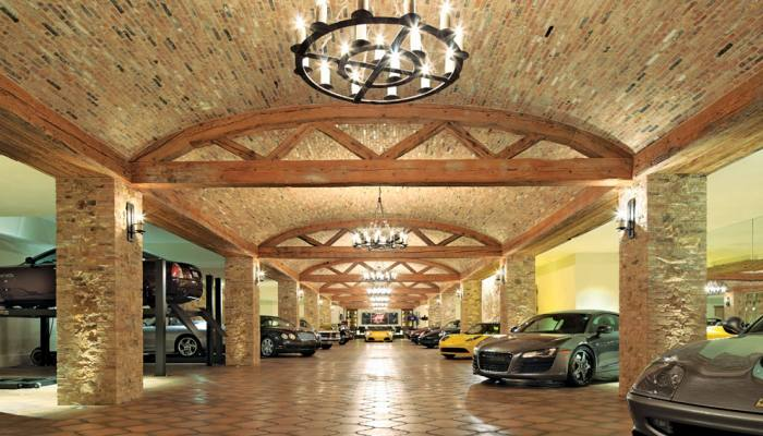 Car collection interior build with buff handmade brick. Exotic cars can be seen along the hall.