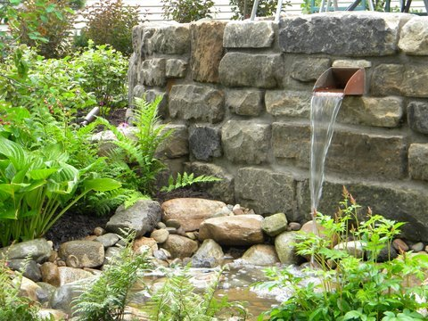 Small man-made waterfall, where the wall of the waterfall was built using Bluestone Cobblestone.