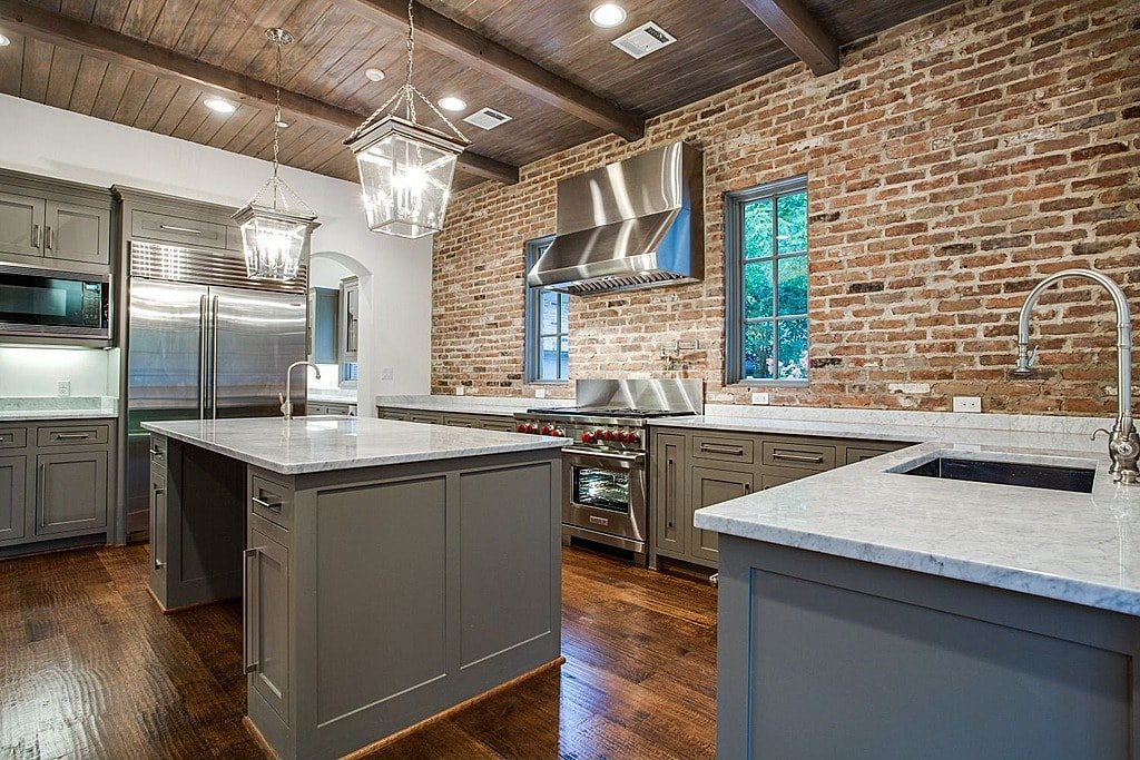 Ample kitchen with island in the middle and Veneer brick used for the wall with windows.