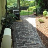 You can see the gate to the backyard and a beautiful walkway paved with Old English Cobblestone.