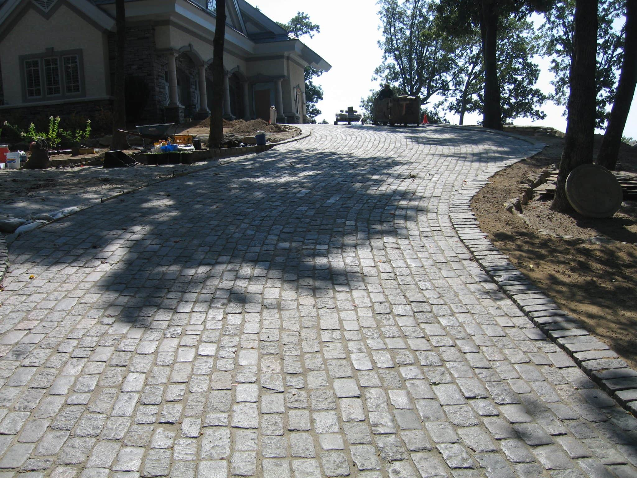 You can see a driveway, paved with Lake Street Cobblestone, leading to a house with a few streets and a roundabout at the top.