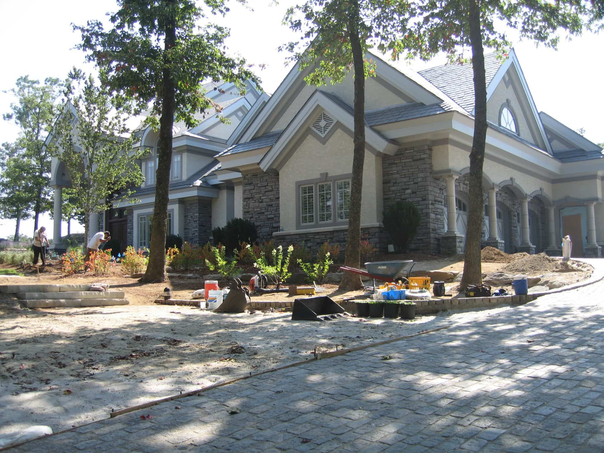 We see a house with a big yard and a driveway paved with Lake Street Cobblestone with a roundabout at the top.