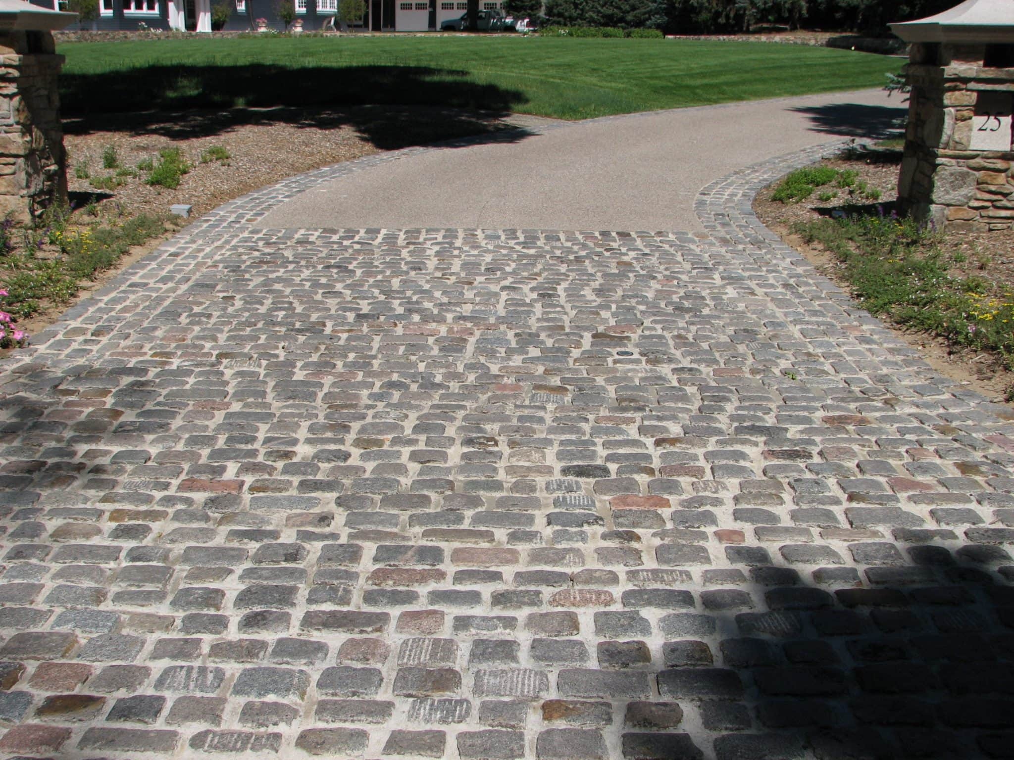 You get a photo facing the outside of a driveway paved with Lake Street Cobblestone.
