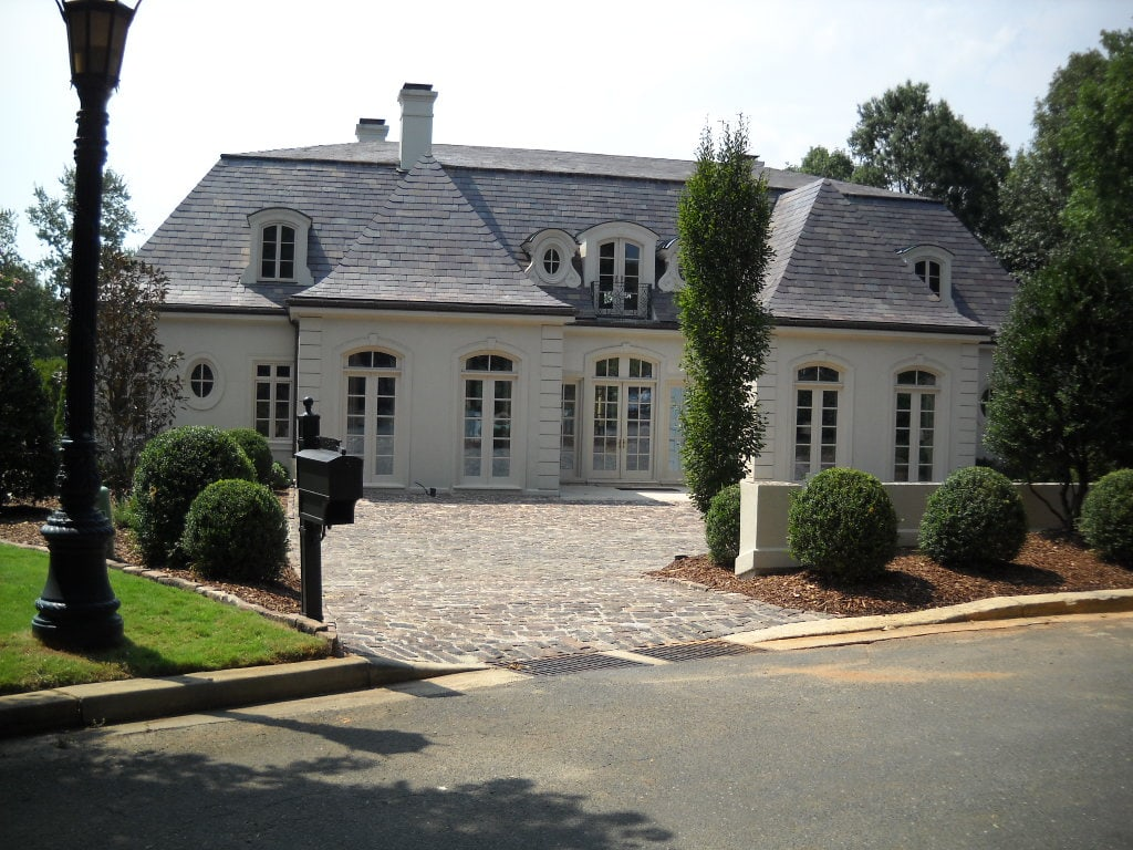 You can view an Old English Cobblestone paved parking area of a big house.