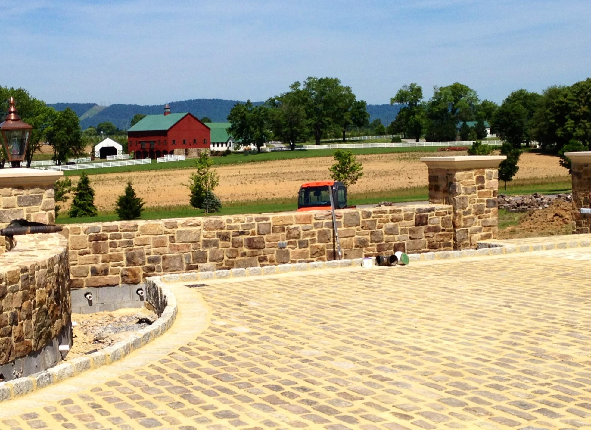 Closer view of the brick wall enclosing the small plaza with the barn house visible on the back.