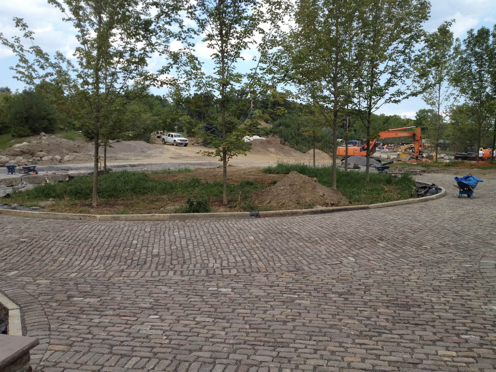 Old English Cobblestone paved roundabout with trees and a green-area in the middle.