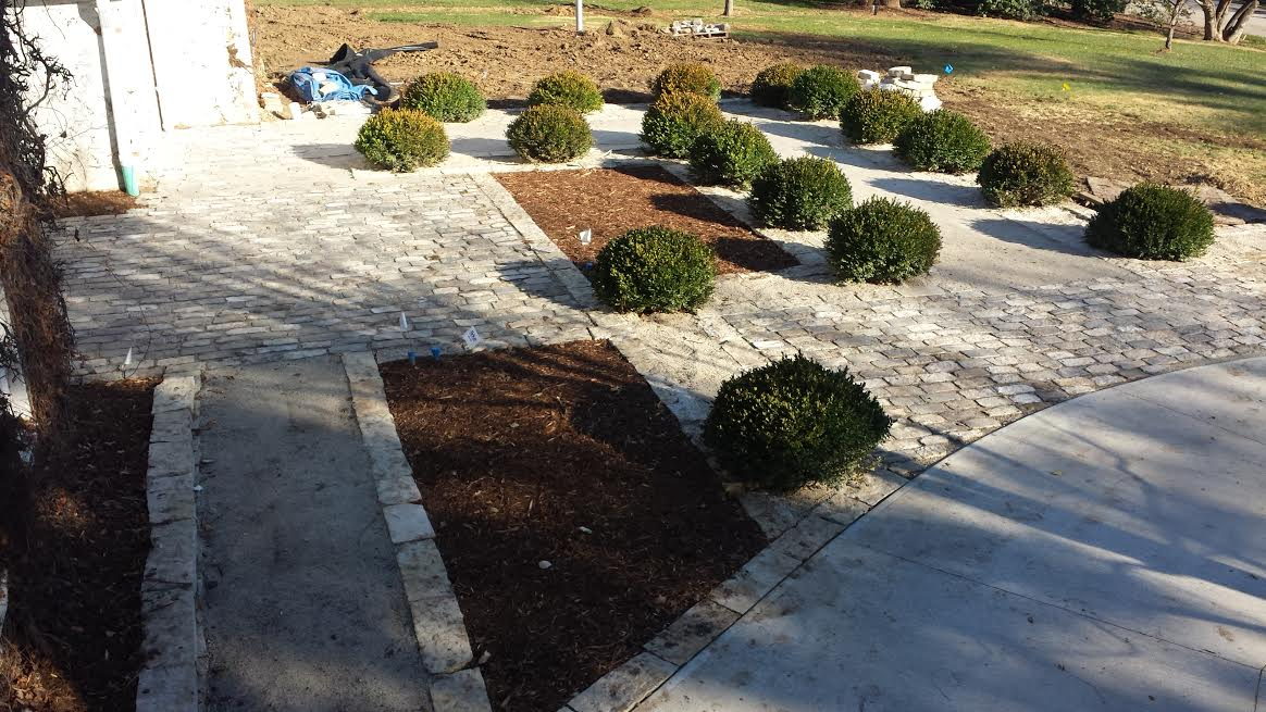 You can view the front walkway of a big house that's paved with Salt and Pepper Cobblestone and has bushes along the edges.