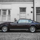 You can view Elton John's Aston Martin V8 from the side view of the driver seat. The car stands in an Old English Cobblestone paved street.