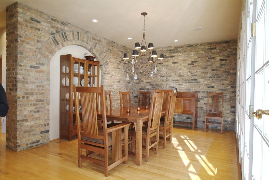 Kitchen area with window opening and Veneer brick wall in the interior of the room.