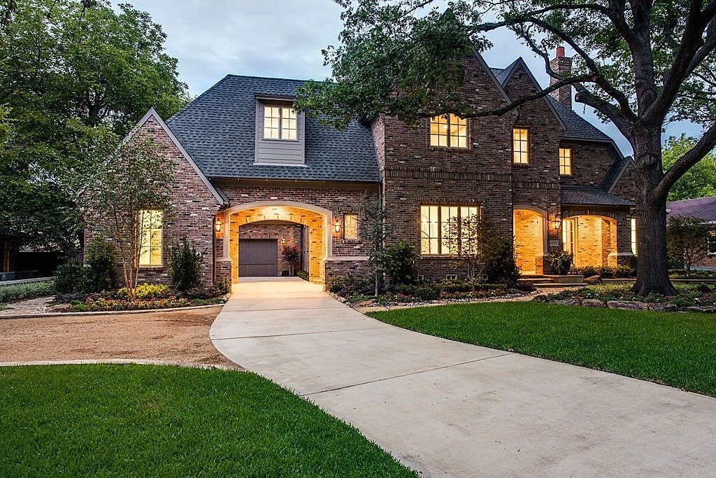 Picture of a driveway leading into a brewery brick built house. It's a beautiful two-story house. The house is surrounded by a green area and a tree outside.