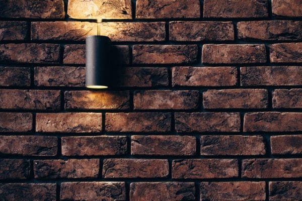 Straight shot of a veneer brick wall with a lamp.