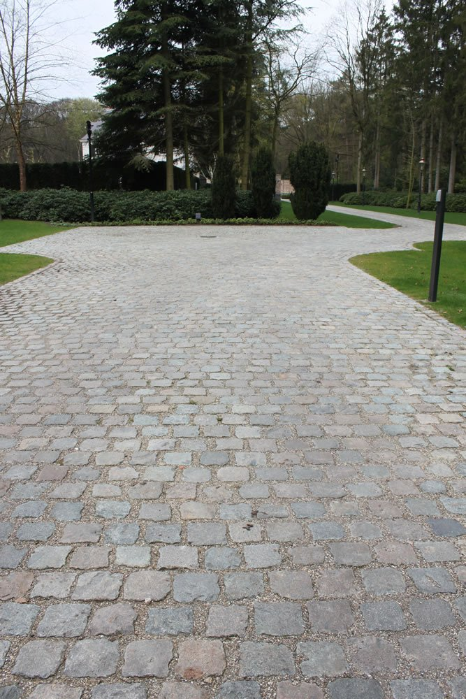 You can view an extensive driveway with turns, paved with Antique European Porphyry Cobbles.