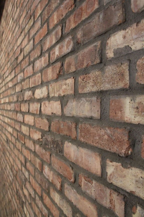 Close-up photo of a veneer brick towards the right facing towards the corner of the room.