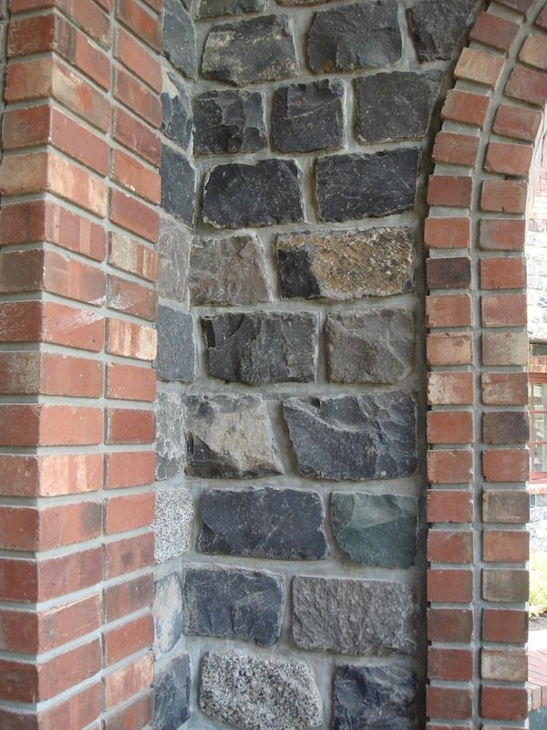 Close-up photo of the corner of a room built with veneer brick with arcades.