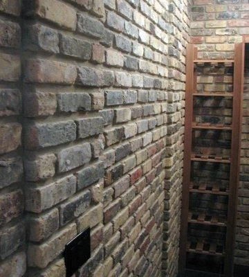 Close-up photo of a Veneer brick wall facing towards the corner of the room.