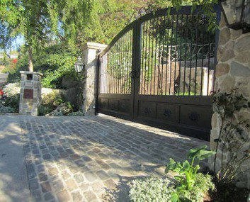Gated entrance built with Antique Bluestone Belgian Block with green areas to the side.