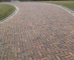 Close up photo of a driveway built with Purington Skinny Pavers. You can see grass on both sides.