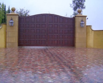 Floor built with Old Tuscany Pavers with a tall gate and two high pillars to the sides.