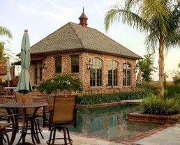 Diagonal view of what seems to be a pool house built with Antique St. Louis Bricks. There's a pool and palm tree visible from this angle.