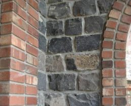 Column of an arch opening built with Old English Stone Veneer. The interior is dark grey stone and the edges are with red bricks.