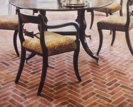 Photo of floor built with Antique Warehouse Red Herringbone Flooring. There's a circular dinner table with wooden chairs around it.