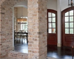Interior columns of a house built with Old Chicago Brick Veneer. They're in arch shape near an entrance. You can see a dinner table in the back and some doors to the right.