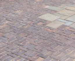 Brick floor built with Antique Capital Pavers and you can see some white bricks in the middle to create an accent effect to the floor.
