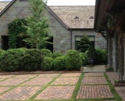 Brick driveway built with Antique Clinton Pavers. It's in a grid layout with green, short grass dividing the square sections on the driveway.