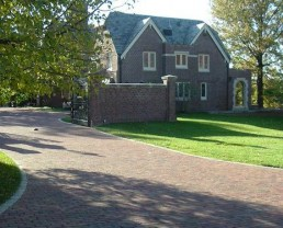 Ample driveway built with Antique Purington Flat Street Pavers leading to the side of the house. The color of the driveway matches perfectly with the house.
