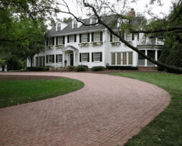 Red brick drive way built withAntique Purington Street Pavers leading to a two-floor white house.