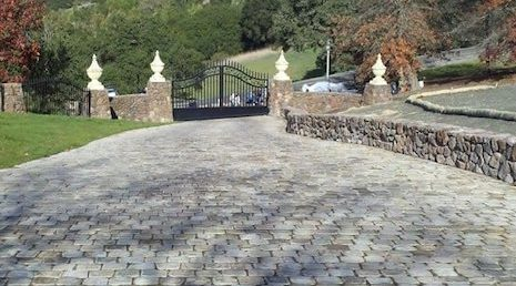 View from the house of an Old Charlottesville Bluestone Cobble driveway that leads down to the gated entrance with a short brick wall to the right.