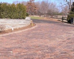 Driveway built with Antique Metropolitan Street Pavers that leads to what seems to be a country house. Because after the brick driveway, there's a paved road with wooden fence to the side.