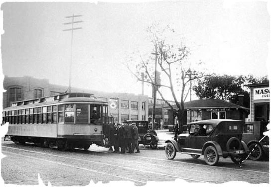 old black and white image of a car and trolly resting above a cobblestone paved street